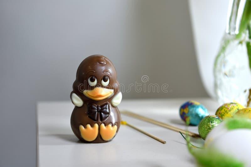 Un canard de chocolat de bébé sur une table avec quelques oeufs de pâques image libre de droits
