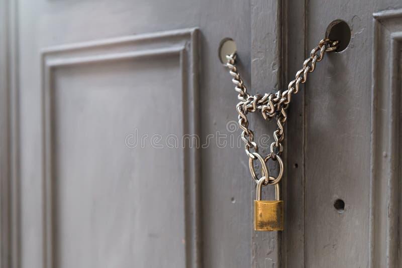 Un candado que sostiene cadenas en una puerta/una puerta foto de archivo libre de regalías