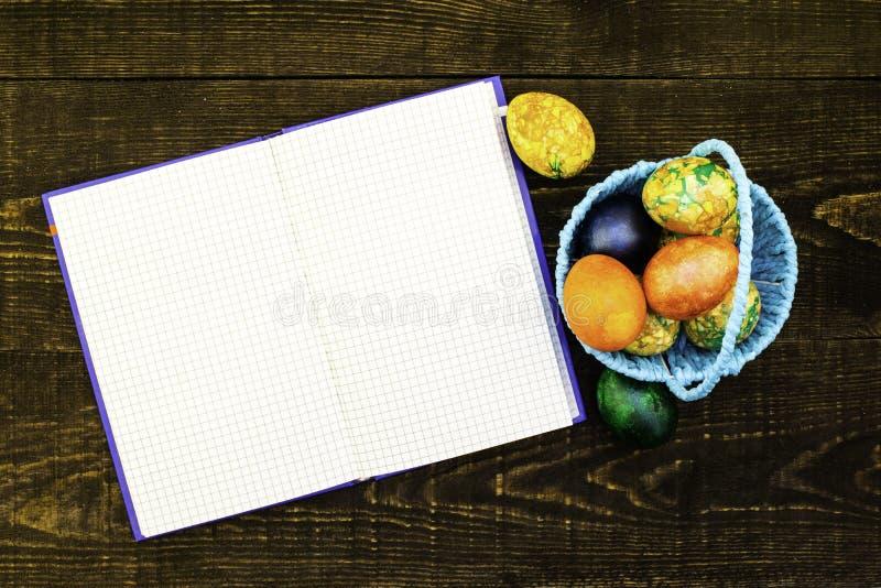 Un canestro blu con le uova di Pasqua e le uova di Pasqua vicine su un fondo di legno marrone scuro, un taccuino in espansione pe immagine stock libera da diritti