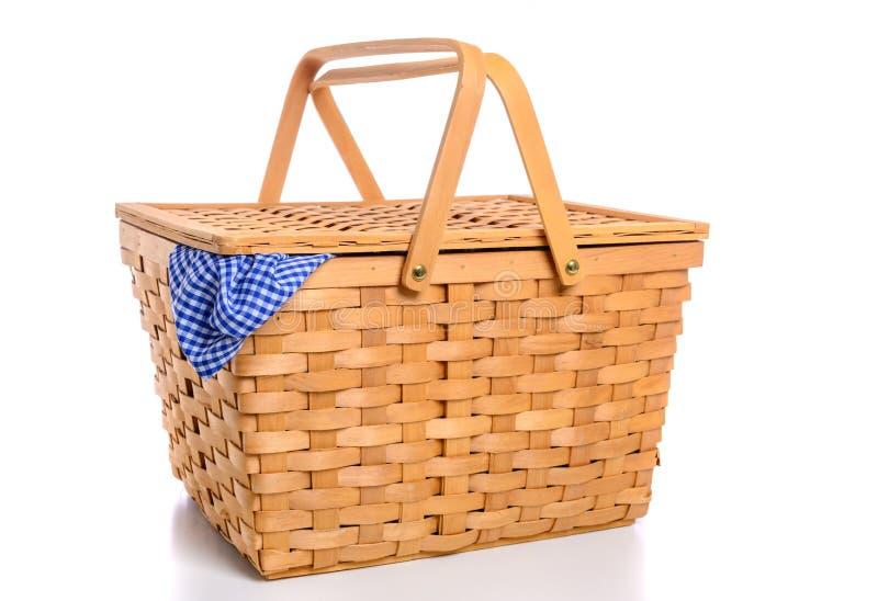 Un canestro di vimini marrone di picnic su un fondo bianco con il panno del percalle fotografie stock