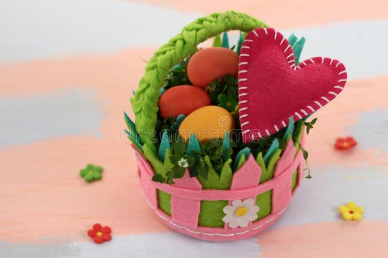 Un canestro ritenuto variopinto luminoso con le uova dipinte e un cuore rosa su un rosa e su un fondo blu-chiaro Fatto a mano da  fotografie stock