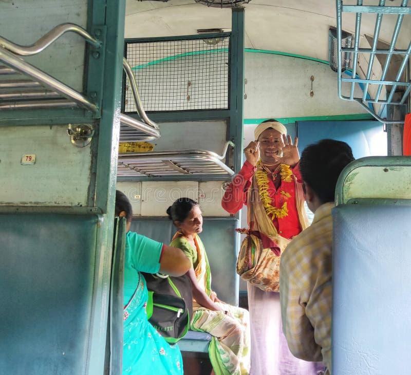 Un cantante folk indiano si esibisce in un treno locale fotografia stock