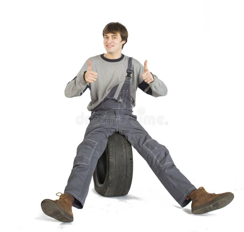 Un capataz moreno joven en uniforme de trabajo del gris con la rueda negra foto de archivo libre de regalías
