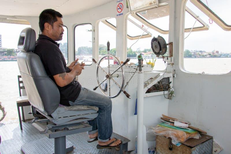 Un capitán está conduciendo un barco en Chao Phraya River foto de archivo libre de regalías