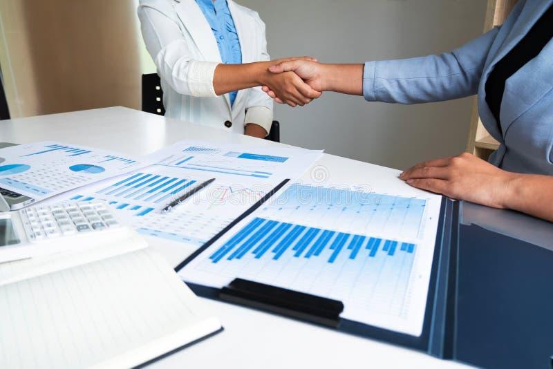 Un capo di due donne di affari che discute i grafici ed i grafici che mostrano i risultati fotografia stock