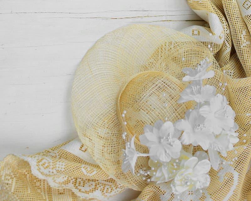 Un capot de paille et des fleurs en soie blanches et enes ivoire sur un fond lavé blanc en bois rustique photo libre de droits
