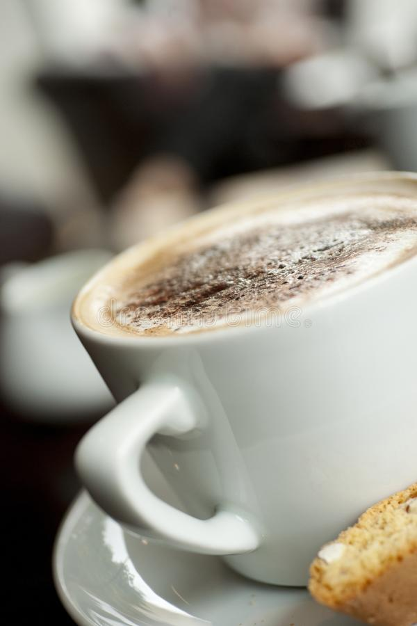 Un cappuccino avec le saupoudrage de chocolat sur la mousse avec un Italien photo libre de droits