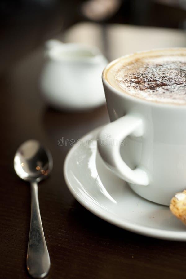 Un cappuccino avec le saupoudrage de chocolat sur la mousse avec un Italien photographie stock libre de droits