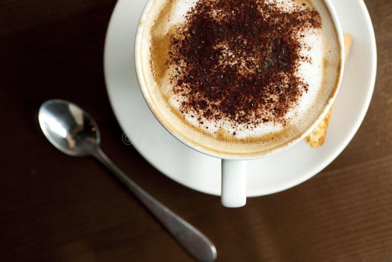Un cappuccino avec le saupoudrage de chocolat sur la mousse avec un Italien image stock