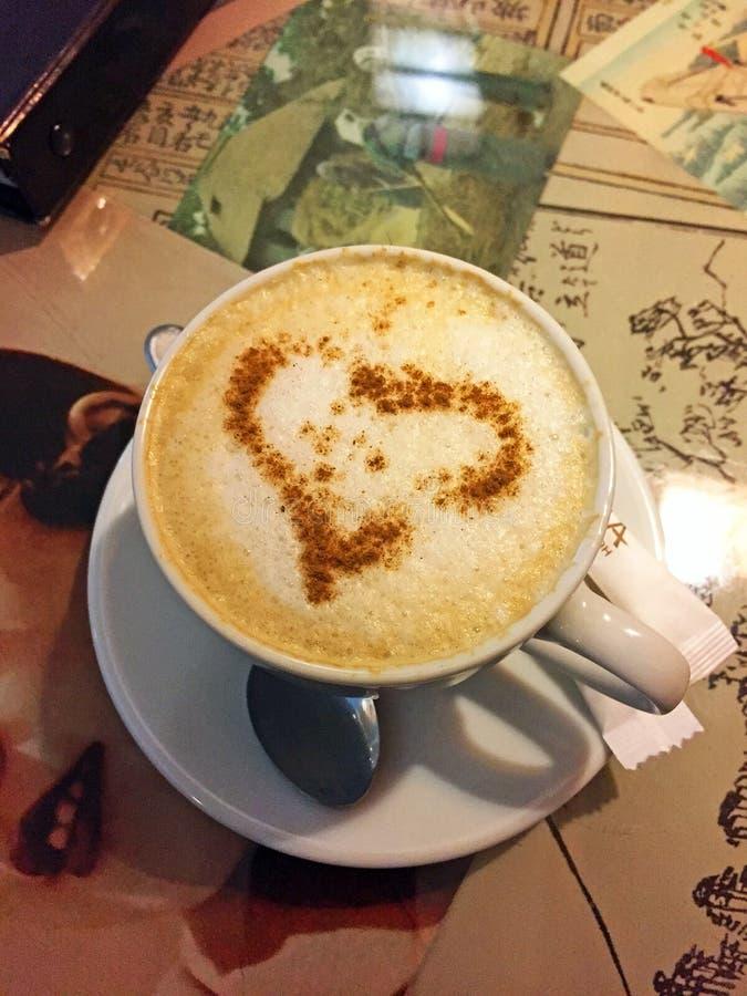 Un cappuccino della tazza di caffè con un cuore di cannella sulla tavola nel caffè fotografie stock