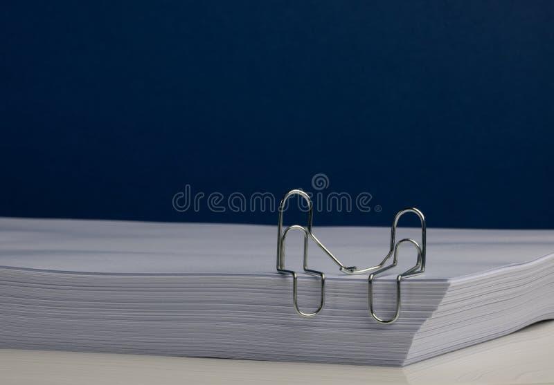 Un carácter del clip de papel junta llevar a cabo las manos en la resma de papel imágenes de archivo libres de regalías