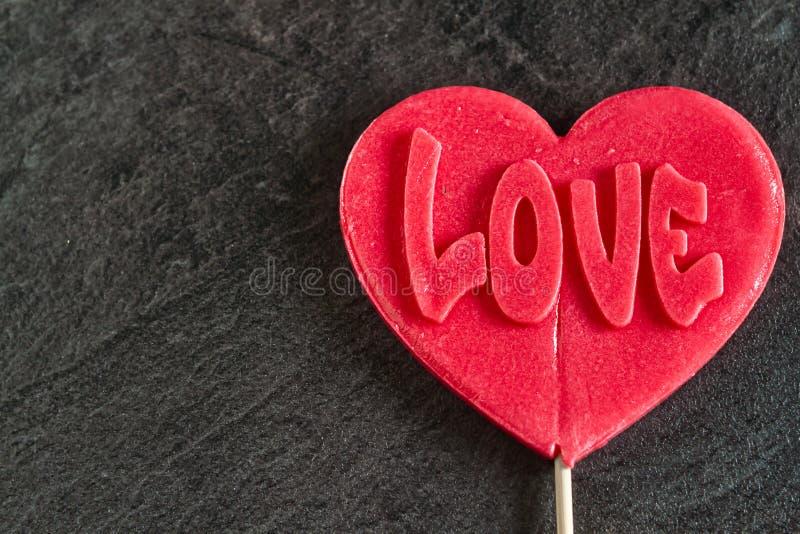 Un caramelo rojo caramelo con inscripción 'amor' fotografía de archivo libre de regalías
