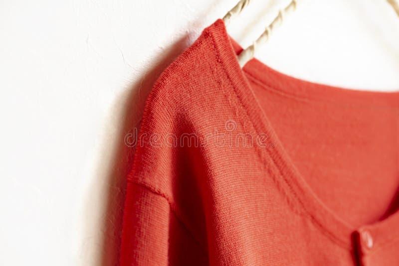 Un cardigan dans accrocher rose orange sur le cintre sur le fond blanc photographie stock libre de droits