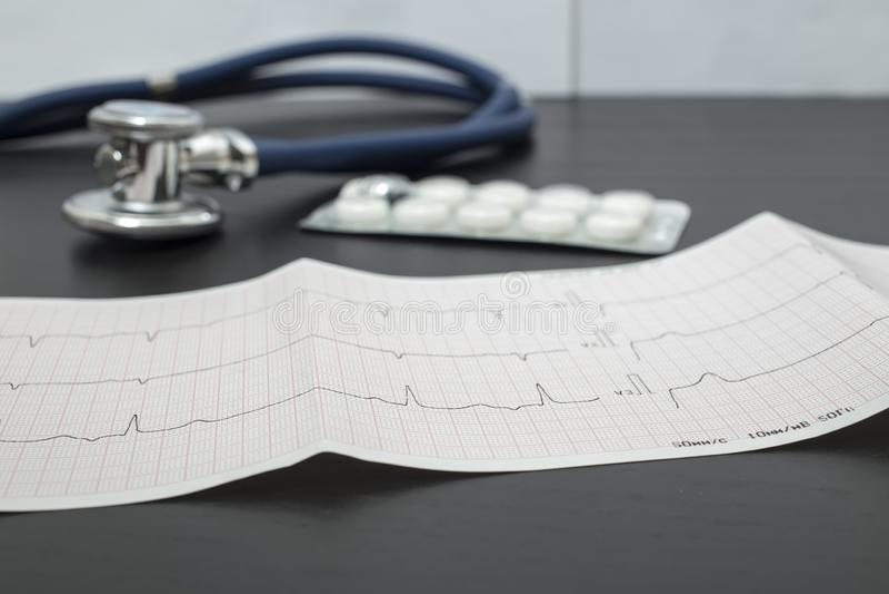 Un cardiogramma, uno stetoscopio blu e le pillole stanno trovando su una tavola scura in un ambulatorio, contro lo sfondo di una  fotografie stock libere da diritti