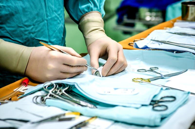 Un cardiosurgeon cuce il canduid da un materiale medico speciale per inserirlo nel cuore paziente del ` s fotografia stock