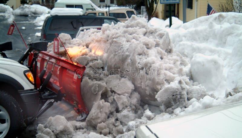 Un cargador de la parte frontal ara una montaña de la nieve después nevadas de 24 de una hora fotos de archivo