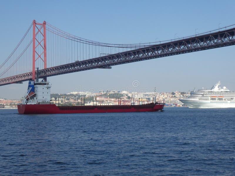 Un carguero rojo y un trazador de l?neas debajo del puente del 25 de abril en Lisboa, Portugal, Europa fotos de archivo