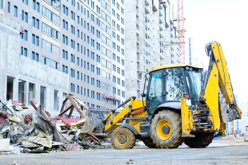 Un caricatore a ruote dell'escavatore a cucchiaia rovescia rimuove l'immondizia sul cantiere, caricante un secchio installato nel fotografia stock