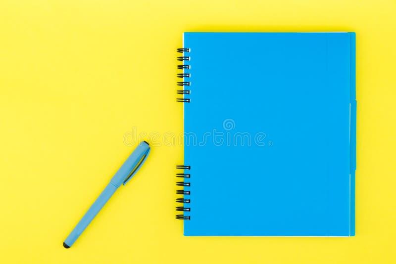 Un carnet bleu avec une poignée sur un fond jaune Calibre plat de configuration Place pour le texte photos libres de droits