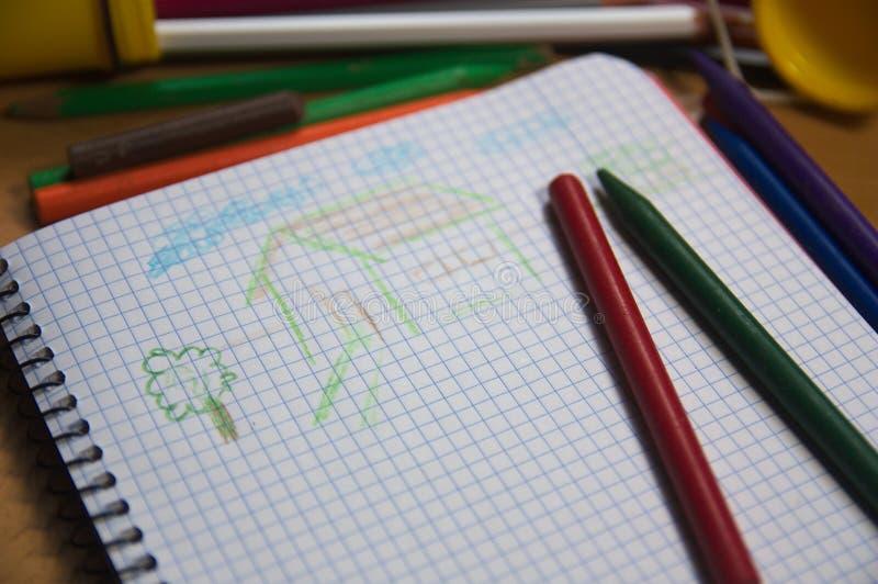 Un carnet d'école où un enfant a dessiné une maison simple image stock
