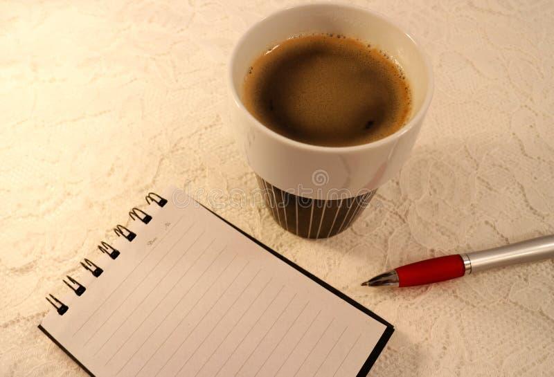 Un carnet de notes à spirale classé par A5, un stylo bille et une tasse de café sur le fond blanc de dentelle photos libres de droits