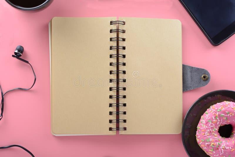 Un carnet des ressorts avec les pages brunes se repose sur un fond rose Autour du bloc-notes il y a des butées toriques de cafés  images libres de droits