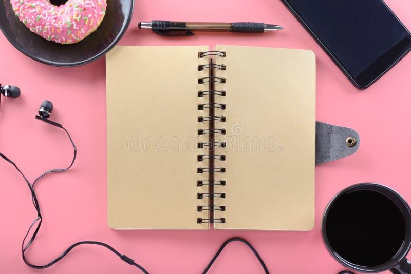 Un carnet des ressorts avec les pages brunes se repose sur un fond rose Autour du bloc-notes il y a des butées toriques de cafés  photos stock