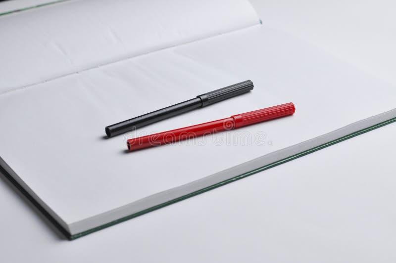 Un carnet et un stylo rouge et noir d'isolement sur un fond blanc Copiez l'espace image libre de droits