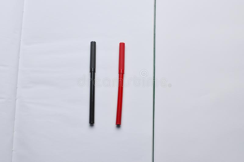 Un carnet et un stylo rouge et noir d'isolement sur un fond blanc Copiez l'espace image stock