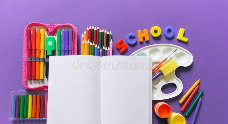 Un carnet ouvert se trouve sur un fond violet Autour des fournitures de bureau sont la couleur de l'arc-en-ciel photo stock
