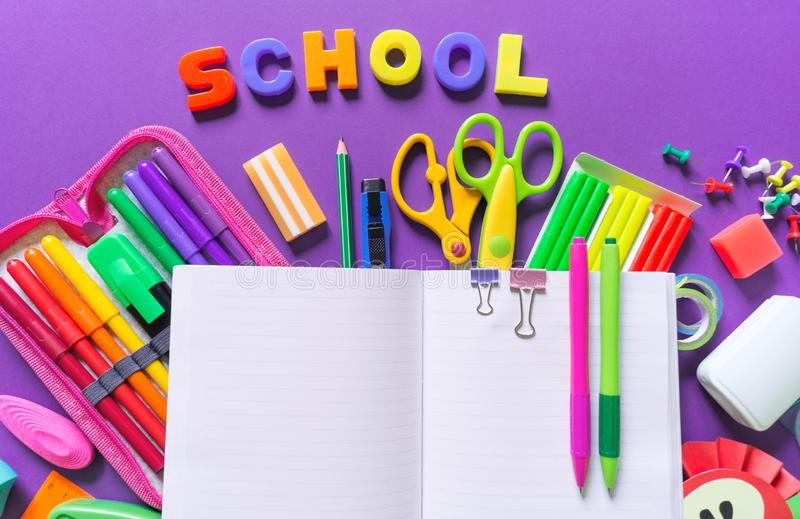 Un carnet ouvert se trouve sur un fond violet Autour des fournitures de bureau sont la couleur de l'arc-en-ciel photographie stock