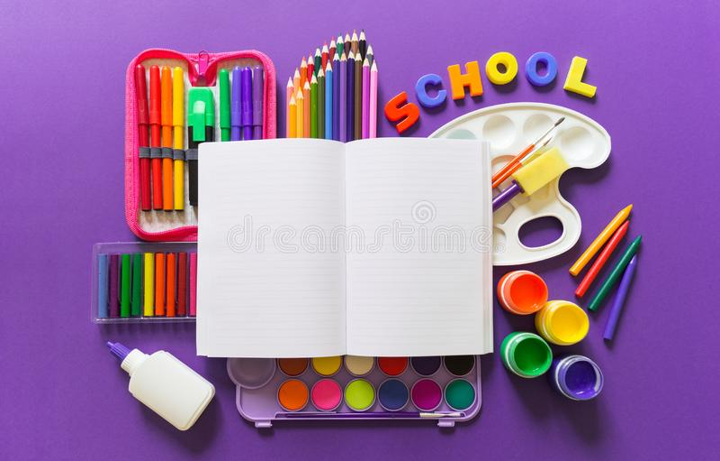 Un carnet ouvert se trouve sur un fond violet Autour des fournitures de bureau sont la couleur de l'arc-en-ciel images stock