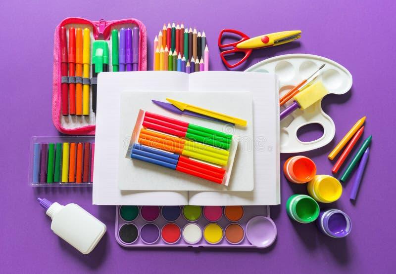 Un carnet ouvert se trouve sur un fond violet Autour des fournitures de bureau sont la couleur de l'arc-en-ciel photo libre de droits