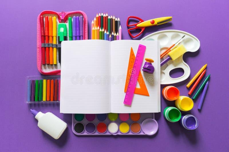 Un carnet ouvert se trouve sur un fond violet Autour des fournitures de bureau sont la couleur de l'arc-en-ciel image libre de droits