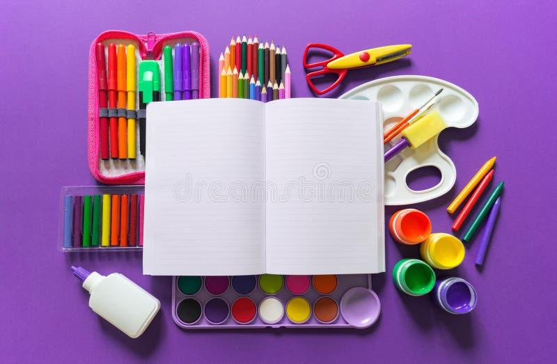 Un carnet ouvert se trouve sur un fond violet Autour des fournitures de bureau sont la couleur de l'arc-en-ciel photos libres de droits