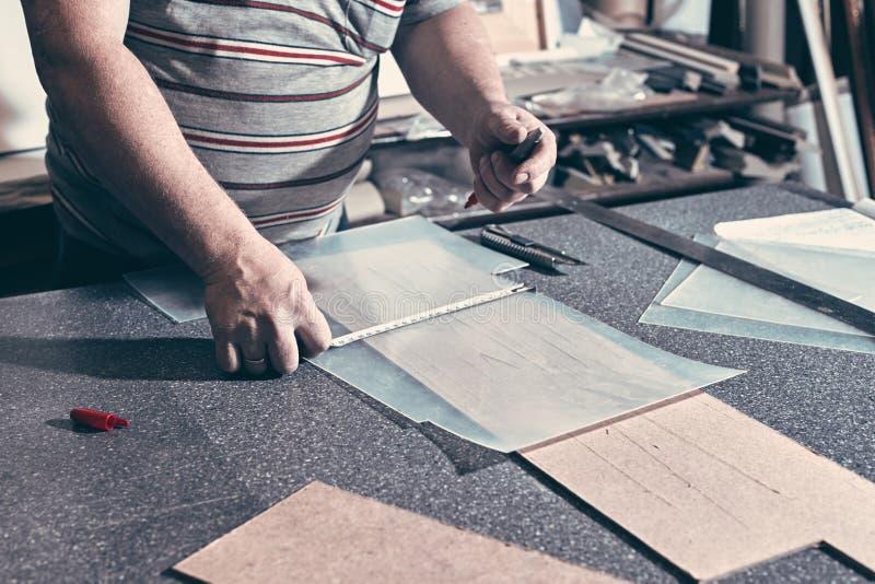 Un carpentiere usa un quadrato dell'inquadratura per il segno del foro in un furnit fotografia stock libera da diritti