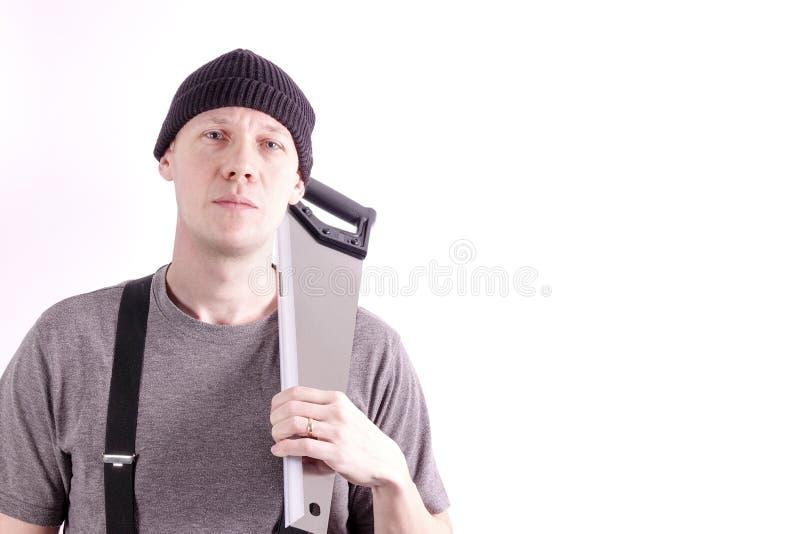 Un carpintero con una sierra sobre el hombro fotos de archivo