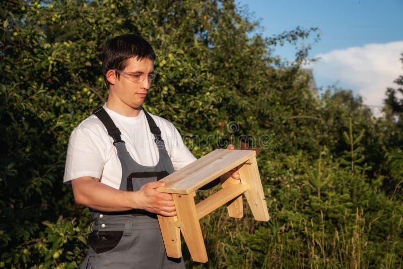 Un carpintero de sexo masculino está sosteniendo un taburete de madera imágenes de archivo libres de regalías