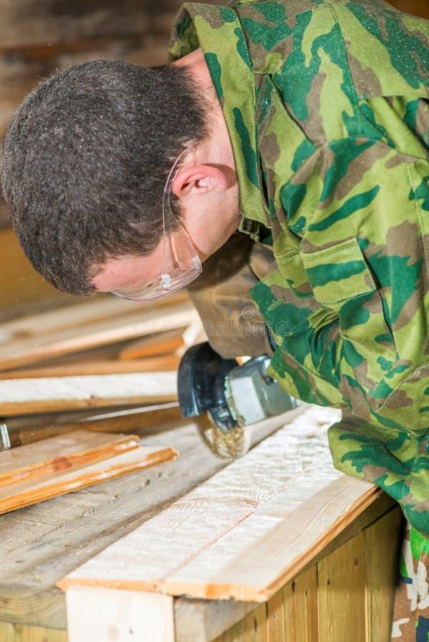 Un carpintero experimentado en gafas procesa la superficie de la boa imagenes de archivo