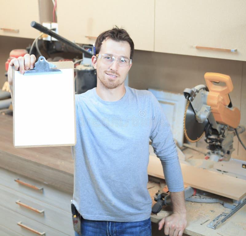 Un carpintero que trabaja difícilmente en la tienda fotos de archivo