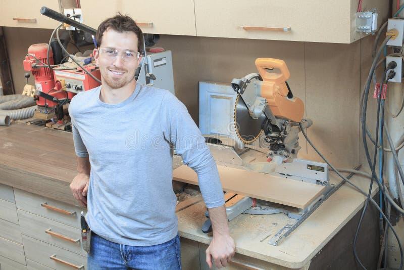 Un carpintero que trabaja difícilmente en la tienda fotografía de archivo