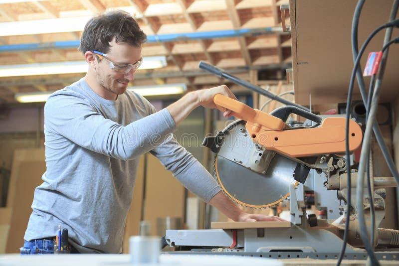 Un carpintero que trabaja difícilmente en la tienda imagen de archivo libre de regalías