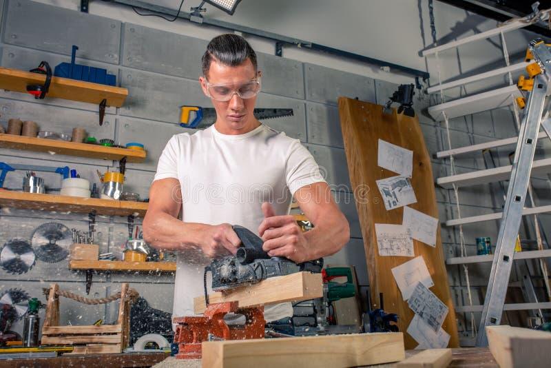 Un carpintero trabaja en carpintería la máquina-herramienta Asierra los detalles de los muebles con una sierra circular Proceso d fotos de archivo libres de regalías