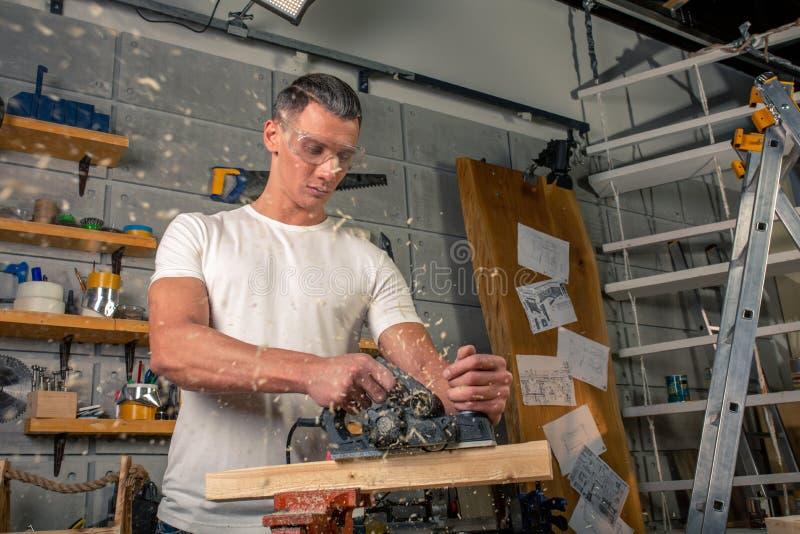 Un carpintero trabaja en carpintería la máquina-herramienta Asierra los detalles de los muebles con una sierra circular Proceso d foto de archivo libre de regalías