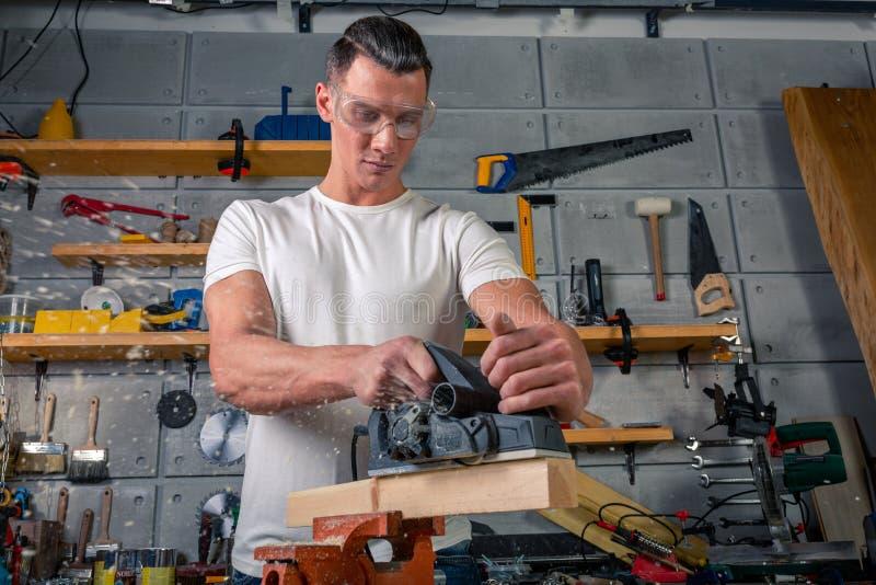 Un carpintero trabaja en carpintería la máquina-herramienta Asierra los detalles de los muebles con una sierra circular Proceso d fotografía de archivo