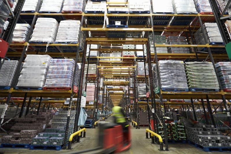 Un carrello elevatore a forcale che passa comunque un magazzino, mosso fotografie stock