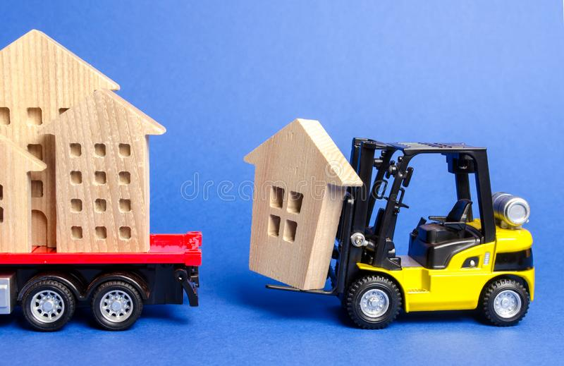 Un carrello elevatore giallo carica una figura di legno di una casa in un camion Concetto di trasporto di carico e del trasporto, immagine stock libera da diritti