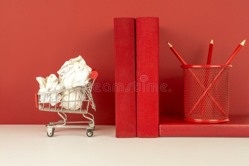 Un carretto con Libro Bianco sgualcito, i libri rossi, matite in un vetro rosso su un fondo rosso e bianco fotografie stock libere da diritti