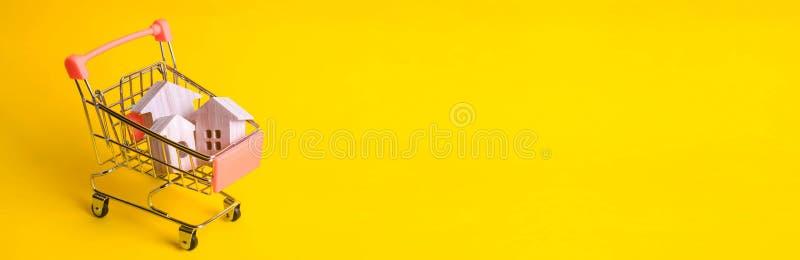 Un carretto del supermercato con le case di legno sta su un fondo giallo Il concetto di acquisto domestico e dell'introduzione su immagine stock