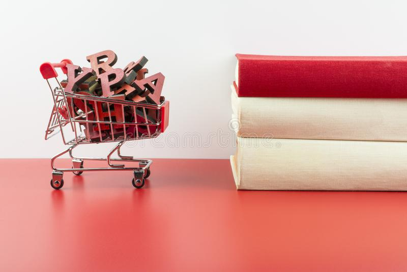 Un carretto riempito di lettere dell'alfabeto inglese e di tre libri su un fondo rosso e bianco fotografia stock